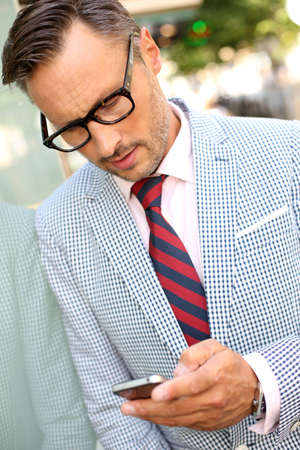 mature men: Man with trendy look reading text message on phone Stock Photo