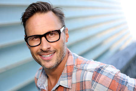 Atractivo hombre alegre con gafas con estilo en