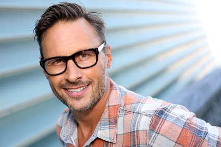 Wesoła atrakcyjny mężczyzna w stylowe okulary na