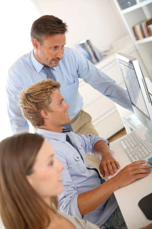 computer class: Young people attending business course with instructor