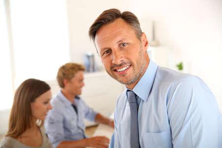 curso de capacitacion: Gerente de negocios con los empleados en el fondo