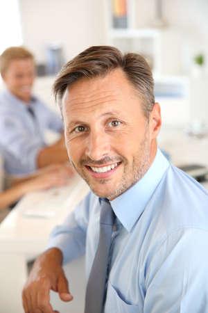 hombre: Gerente de negocios con los empleados en el fondo