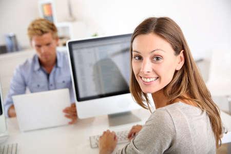 secretary office: Portrait of smiling office worker in front of desktop