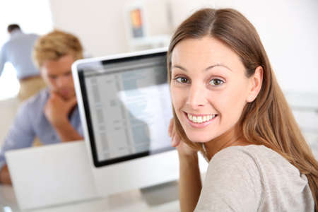 Portrait of smiling office worker in front of desktop photo