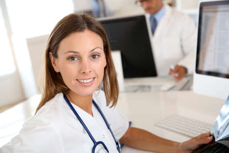 doctor computer: Beautiful nurse working in hospital office Stock Photo