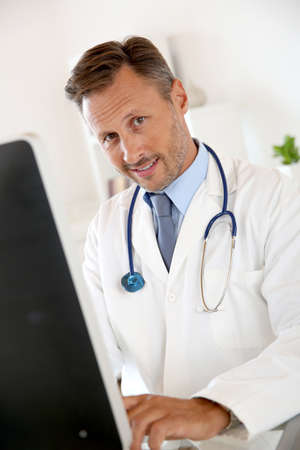 medicalcare: Portrait of smiling doctor sitting in front of computer