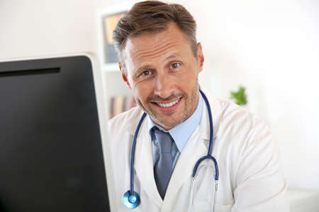 Portrait of doctor sitting in front of computer Stock Photo - 22085880