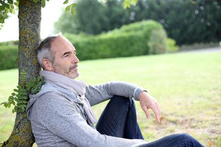 quietness: Senior man sitting in park and enjoying quietness