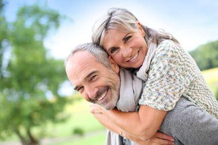 Senior man giving piggyback ride to woman photo