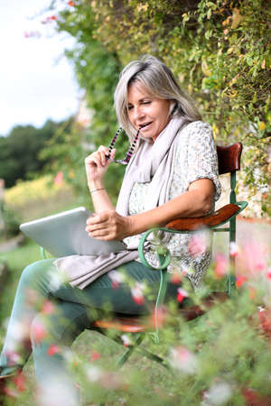 Senior woman using digital tablet in home garden photo