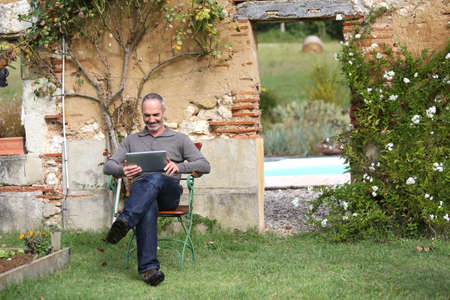 websurfing: Senior man relaxing with tablet in private garden Stock Photo