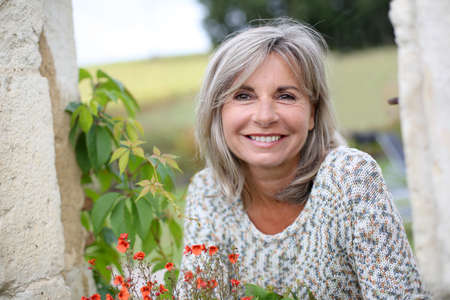 mujer: Retrato de mujer madura, serena en el jardín