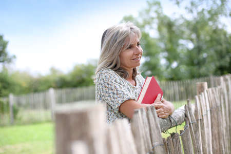 garden fence: Senior woman standing by fence with book in park Stock Photo