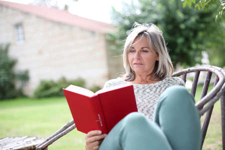 Senior woman relaxing in chair with novel photo