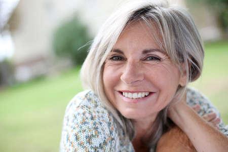 sonrisa: Retrato de mujer madura, serena en el jard�n