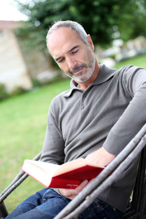 Senior man reading novel in country home garden photo