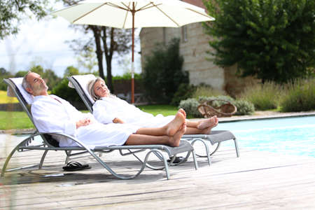 thalasso: Senior couple in spa hotel relaxing in long chairs