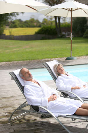 Senior couple in spa hotel relaxing in long chairs photo