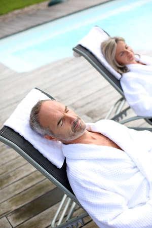 thalasso: Senior couple à l'hôtel spa de détente dans des chaises longues