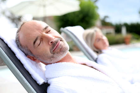 thalasso: Senior man in spa hotel relaxing in long chair Stock Photo