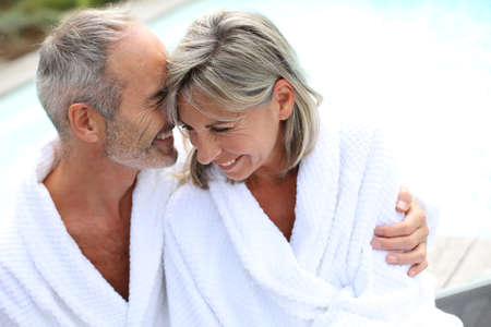 bathrobes: Happy senior couple in bathrobe by resort pool