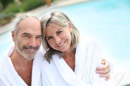 thalasso: Heureux couple senior en peignoir de piscine de l'hôtel Banque d'images