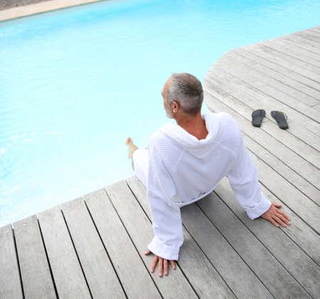 thalasso: Senior man with spa bathrobe relaxing by pool