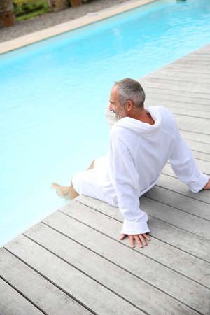 thalasso: Senior homme avec spa peignoir de détente près de la piscine