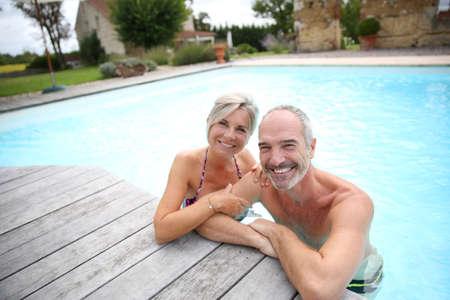 active people: Active senior couple in resort pool