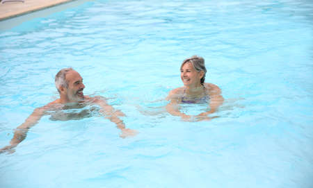 Active senior couple in resort pool photo