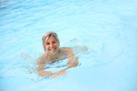 Cheerful senior woman in swimming-pool