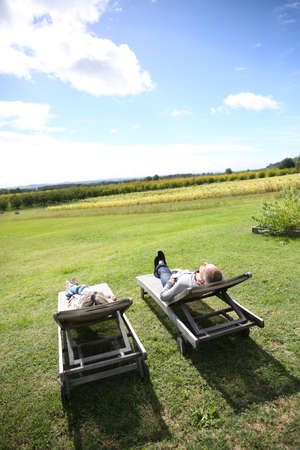 Senior people relaxing in long chairs in countryside Stock Photo - 22394770