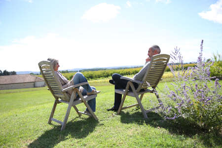 Senior people relaxing in long chairs in countryside Stock Photo - 22394772