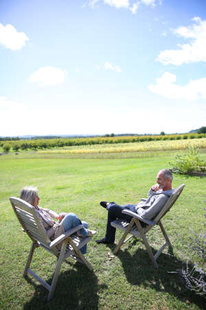 Senior people relaxing in long chairs in countryside photo