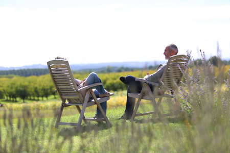 long weekend: Senior people relaxing in long chairs in countryside Stock Photo