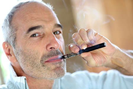 smoking a cigarette: Portrait of senior smoker with electronic cigarette Stock Photo