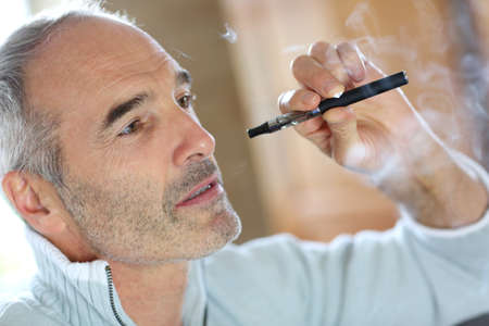 senior smoking: Portrait of senior smoker with electronic cigarette Stock Photo