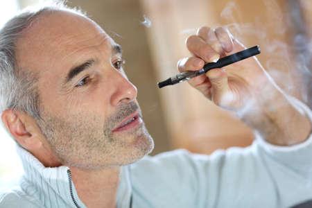 hombre fumando: Retrato de fumador mayor con el cigarrillo electrónico