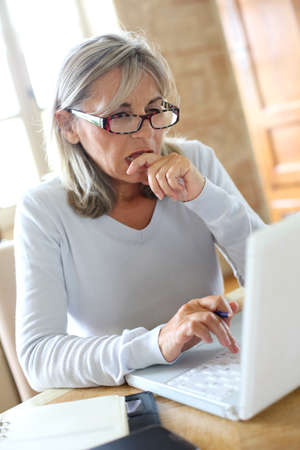 perplexed: Perplexed senior woman in front of laptop