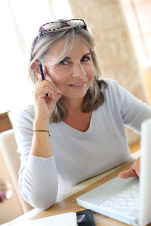 Senior woman at home figuring out income tax  Stock Photo - 22395753