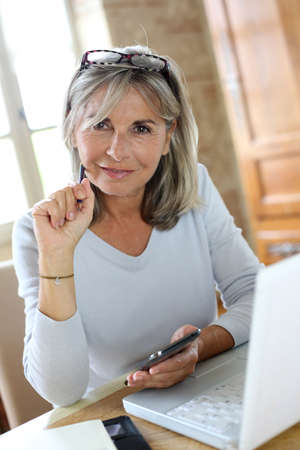 figuring: Senior woman at home figuring out income tax