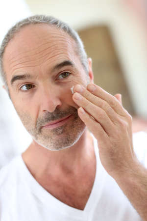 Mature man in front of mirror applying cosmetics photo