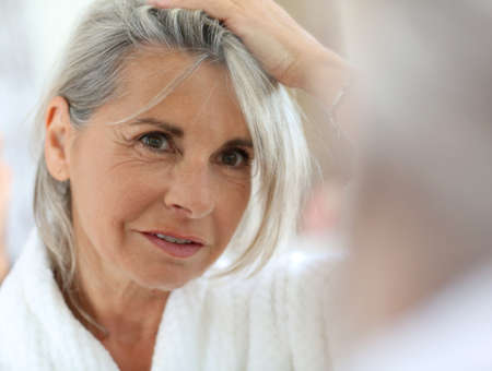 woman in the mirror: Senior woman worried by hair getting grey Stock Photo