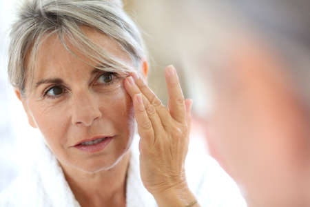 Senior vrouw toepassing van anti-rimpels crème Stockfoto