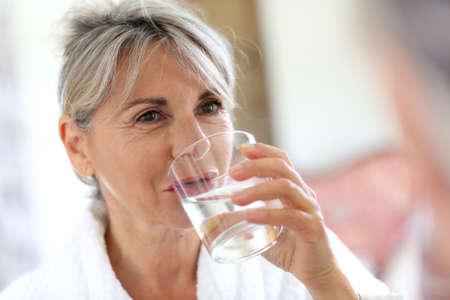 Senior vrouw drinkwater in de ochtend