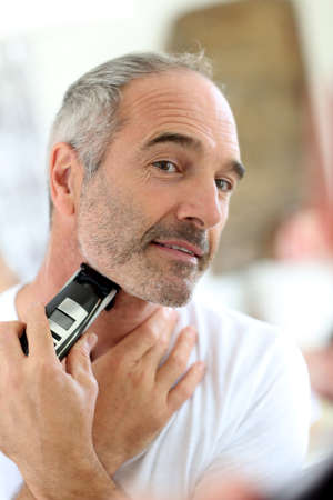 beautycare: Senior man shaving beard with electric razor Stock Photo