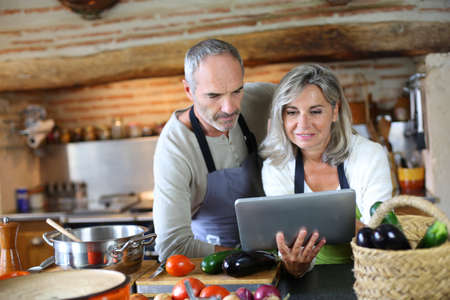 woman cooking: Senior couple in home kitchen looking at tablet Stock Photo