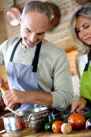 Senior couple in kitchen preparing dinner photo