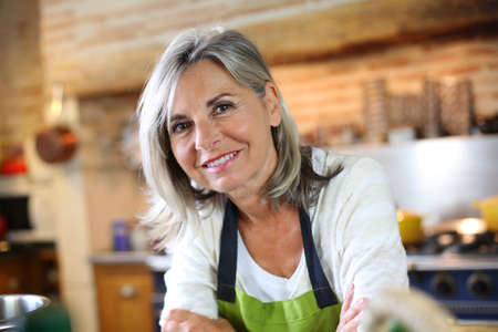people cooking: Portrait of senior woman in home kitchen