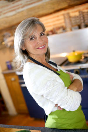Portrait of senior woman in home kitchen photo